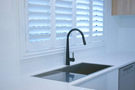 Modern kitchen with sink and plantation shutters