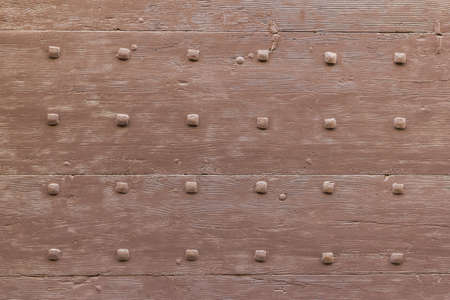 into: Row of nails driven into an old door.