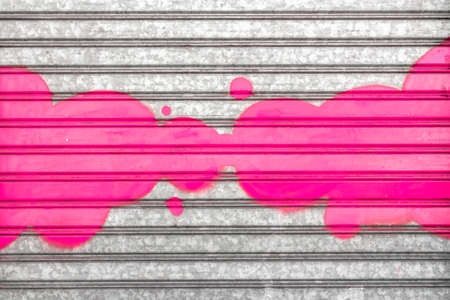 background: A pink cloud painted with spray paint on a roller shutter.
