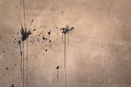 splashed: Splashes of black paint on an old wall.