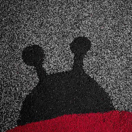linoleum: The silhouette of a ladybug on linoleum. Stock Photo
