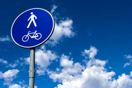 a two wheeled vehicle: A sign Indicates the presence of a pedestrian and bicycle trail.