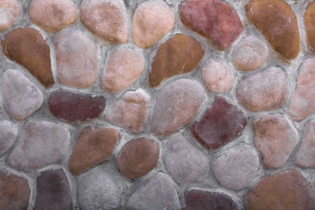 manner: Stone wall composed of oval stones arranged in an irregular manner. Stock Photo