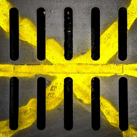 Detail of a manhole with yellow X drawn with paint spay. photo