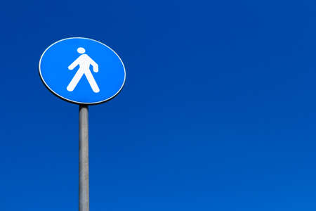 A sign of European pedestrian crossing, isolated on blue sky background. photo