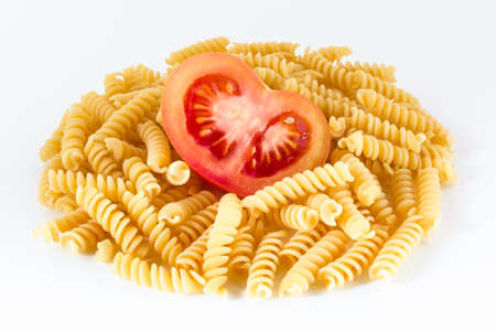 designates: Bunch of pasta with tomato cut in half on a white background. Stock Photo