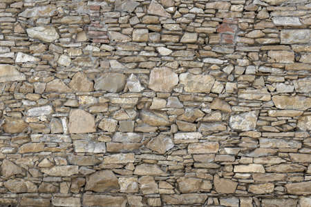 Front view of a wall made up of irregular stones.