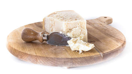 flaked: Wooden cutting board with flaked Parmesan.
