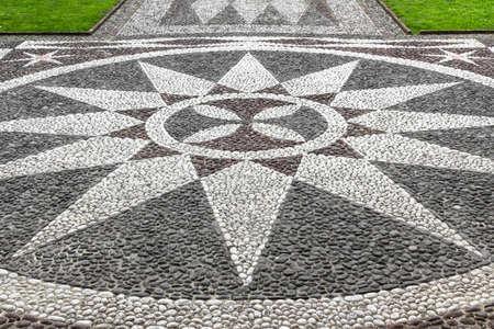 esoterismo: Un mosaico de piedra que representa una estrella de doce puntas, ubicado en la entrada de una iglesia.