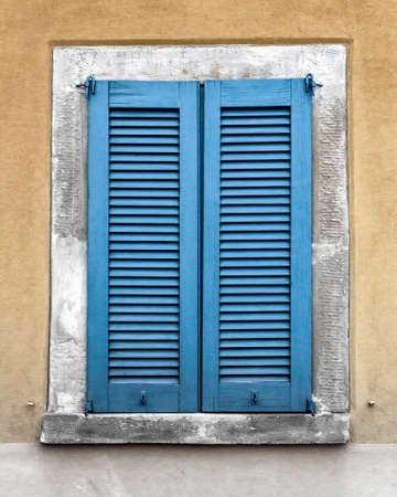 window view: Vertical view of an old blue window on yellow wall Stock Photo
