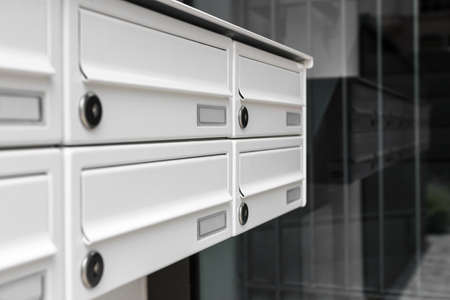 mailbox: Mailboxes, with a modern design, positioned at the entrance of an apartment building.