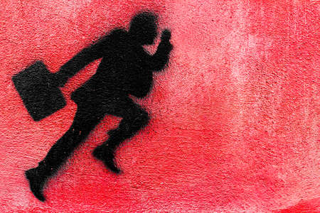 hurried: Graphical representation of a runner businessman on a plastered wall. Stock Photo