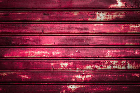 old metal: Front view of a shutter rusted pink, deteriorated from elements.