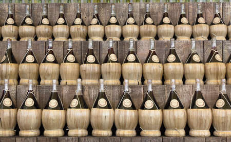 rakia: Front view of a series of jars for wine, arranged in a row on three levels.