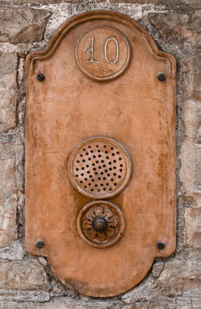 intercom: Front view of an old intercom located in a brick wall.