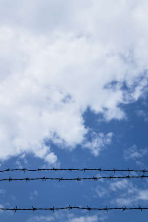military shield: Barbed wire fence with blue sky and clouds in the background. Stock Photo