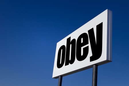 Big ad panel, embossed with the order to obey, isolated on blue sky.