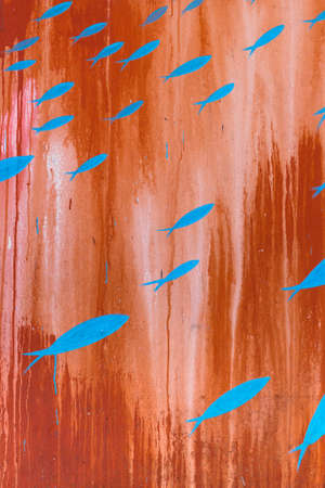 flyaway: Pattern of blue fish painted on a vertical rusty panel. Stock Photo