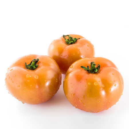 thorough: Three tomatoes covered with drops of clear water, after a thorough cleaning.