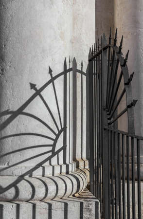 solidity: A classical column with shadows of the protective railing, concept of solidity and stability.