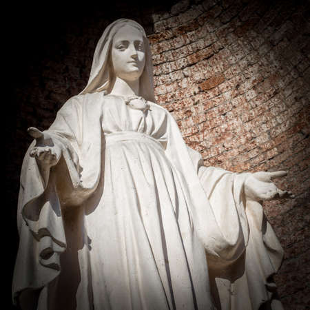 Statue of Virgin Mary in the Roman Catholic Church on wall background.