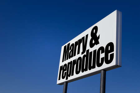 reproduce: Big ad panel, embossed with the message Marry and reproduce, isolated on blue sky. Stock Photo