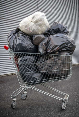 consumerism: A shopping cart full of garbage bags. A representation of consumerism and trash food.