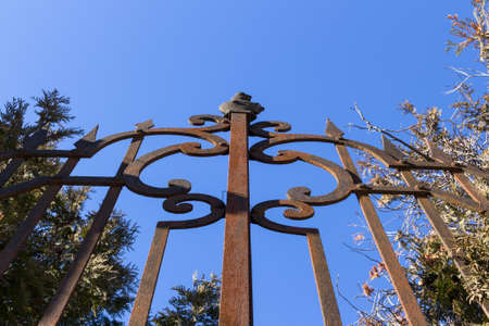 entrance gate: Close-up of wrought-iron rusted fence against blue sky