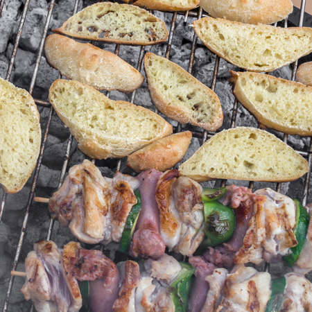 barbecuing: Bar-B-Q or BBQ with kebab cooking. Coal grill of chicken meat skewers with slices bread. Barbecuing lunch. Top view. Stock Photo