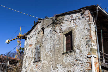 crane parts: Big old abandoned house with rotten windows, in renovation. A yellow crane on the background. Stock Photo