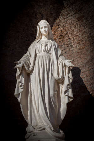 壁の背景にローマ カトリック教会の神聖な女性の像。
