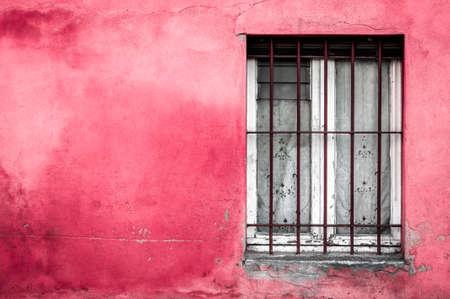 fuchsia: Old typical Mediterranean window on fuchsia stucco wall.