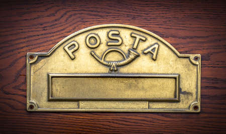 Old Italian mailslot with traditional symbol of trumpett and message Posta (Mail).