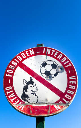 exclude: Sign prohibiting access to the dogs and to play football. They are well see two bullet holes. Stock Photo