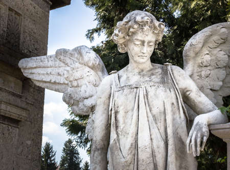 weeping angel: Statue of an weeping angel leaning at a grave Stock Photo