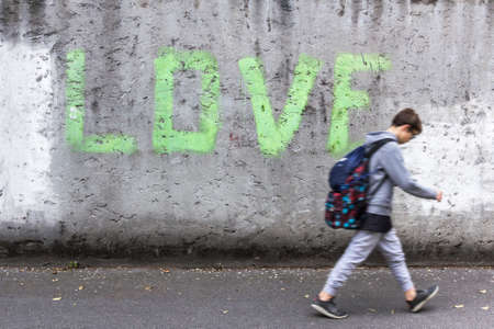 head bowed: A schoolboy walking down the street with head bowed; on the wall stands the inscription LOVE.