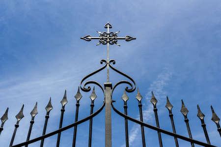 Schmiedeeisernes Tor mit Kreuz gegen den blauen Himmel