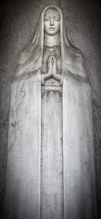 clasped hands: Old statue of Virgin Mary with clasped hands Stock Photo
