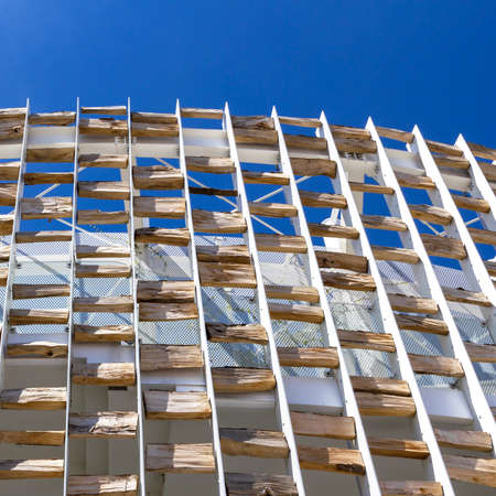 Modern building decorated with wooden logs. Excels the contrast between the modern style and the elements of nature.