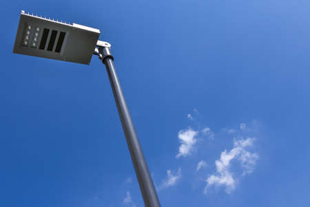 Modern street lamp against blue sky and clouds