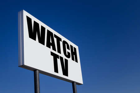 Big ad panel, embossed with the message WATCH TV, against blue sky.
