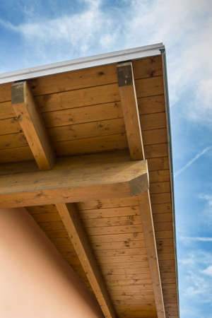 joist: Corner of house with wooden beams against blue sky. Stock Photo