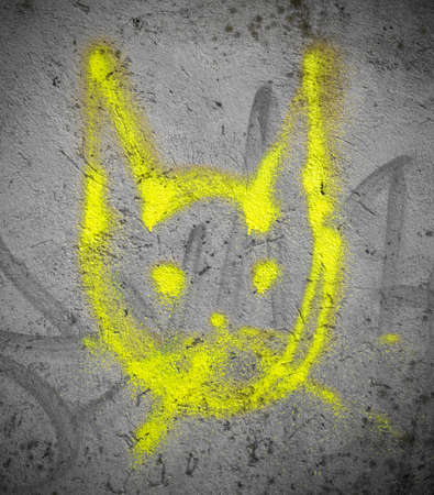 wall paint: Street art by unknown artist of a yellow creature resembling a cat. Stock Photo