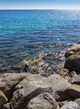 sanremo: Amazing sea with blue summer wave and rocks. Summer sea background. Endless sea. Daylight sea. Turquoise sea. Sea foam and brown rocks. Sunny day sea view. Sea rock.