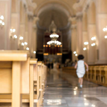 A little girl runs to church, heading for the altar. Defocused blurry background.