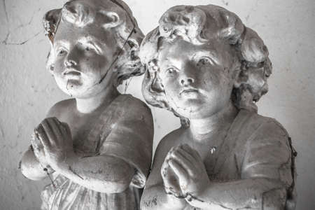 cobwebs: Statues of children in prayer covered with cobwebs.