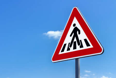 Pedestrian crossing sign against blue sky background Stock Photo