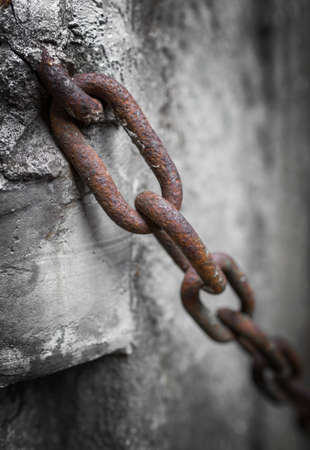 Rusty chain anchored to the cement pole. Defocused blurry background. Stock Photo