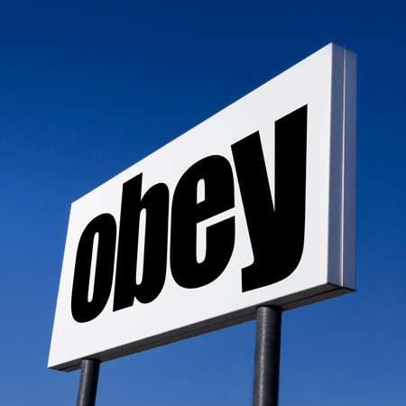 Horizontal billboard with the order to OBEY, against irreal blue sky. Abstract concept of consumerism, human mind control, power of corporations and lobbies.