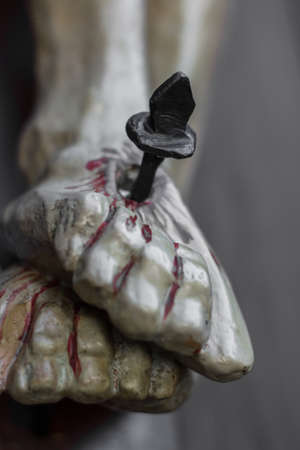 stigmata: Closeup of feet of Jesus Christ nailed to the cross during the crucifixion. Shallow depth of field. Defocused blurry background. Stock Photo
